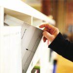 A hand pulls a design book off a shelf